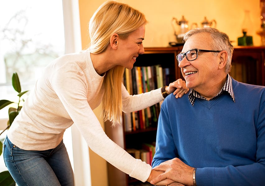A happy male resident wearing glasses pats one hand of a caregiver who has her other hand on his shoulder.