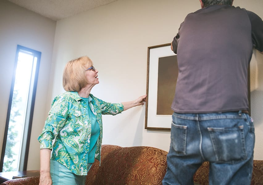 A man helps a senior woman hang artwork on the wall of her assisted living apartment.