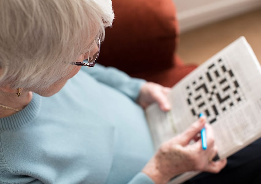 A senior resident does a crossword puzzle while she sits on an armchair in her private apartment.