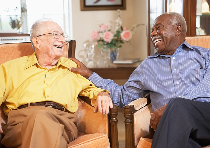 Two men sitting in armchairs talk and laugh together in an assisted living facility.