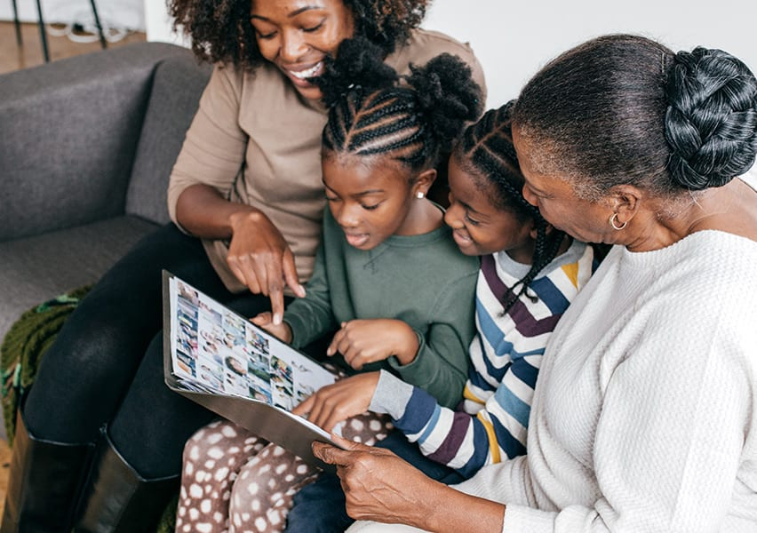 A grandmother looks at a photo album with her daughter and two granddaughters while sitting together on the sofa.