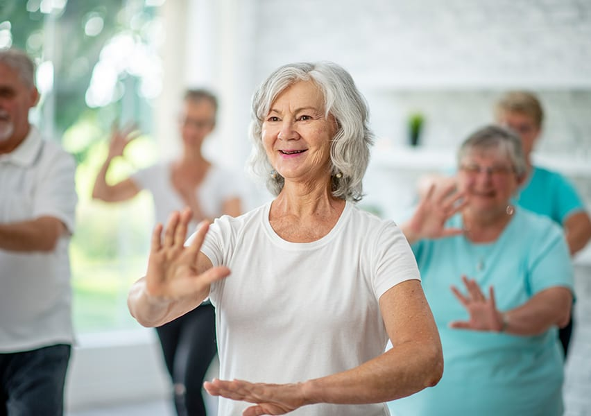 A group of seniors do tai chi together for exercise.