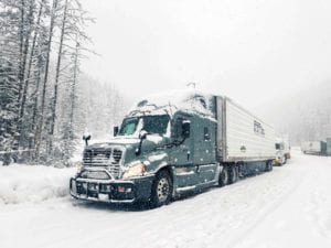 A Prime refrigerated division truck drives through the snow.