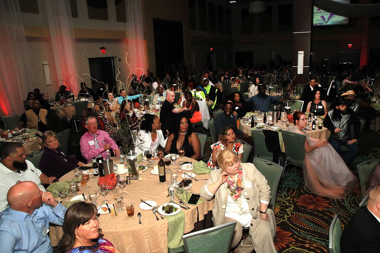 Female truck drivers and their families sitting in a ballroom, while being celebrated during Prime Inc,'s annual Highway Diamonds Gala.