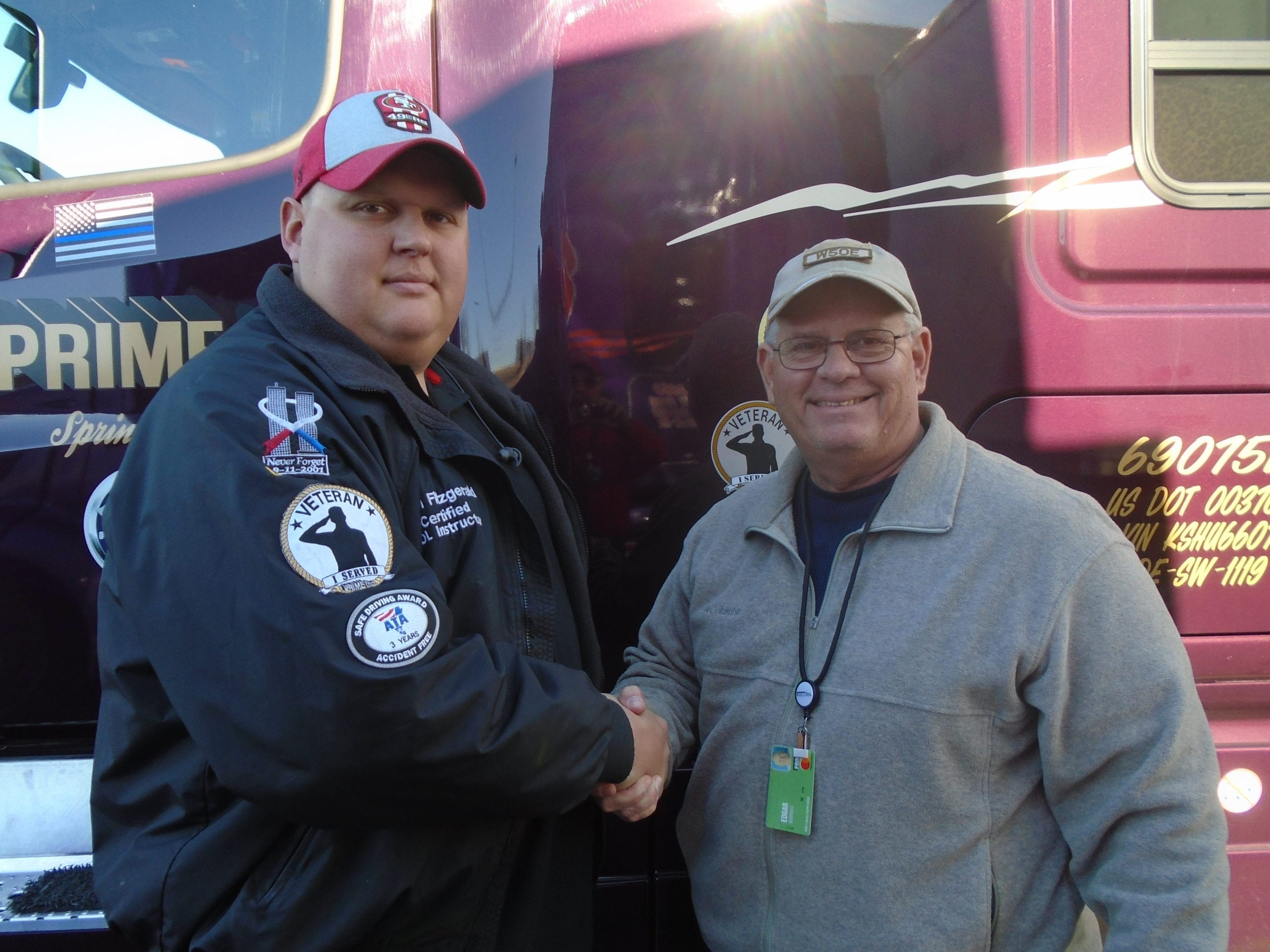 Prime driver and instructor shake hands in front of semi-truck.