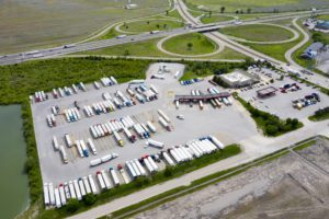 Aerial view of a Missouri highway and truck stop with rows of parked semi trucks.