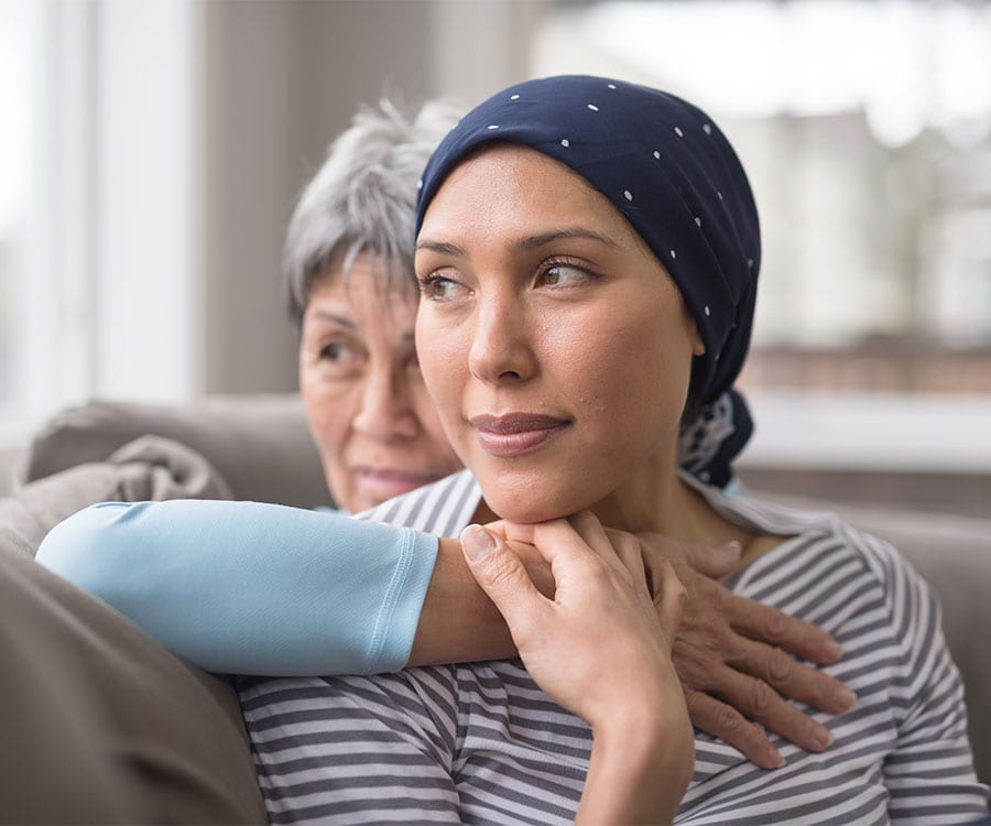 A younger patient and older family member sit holding each other, gazing outward through a window together.