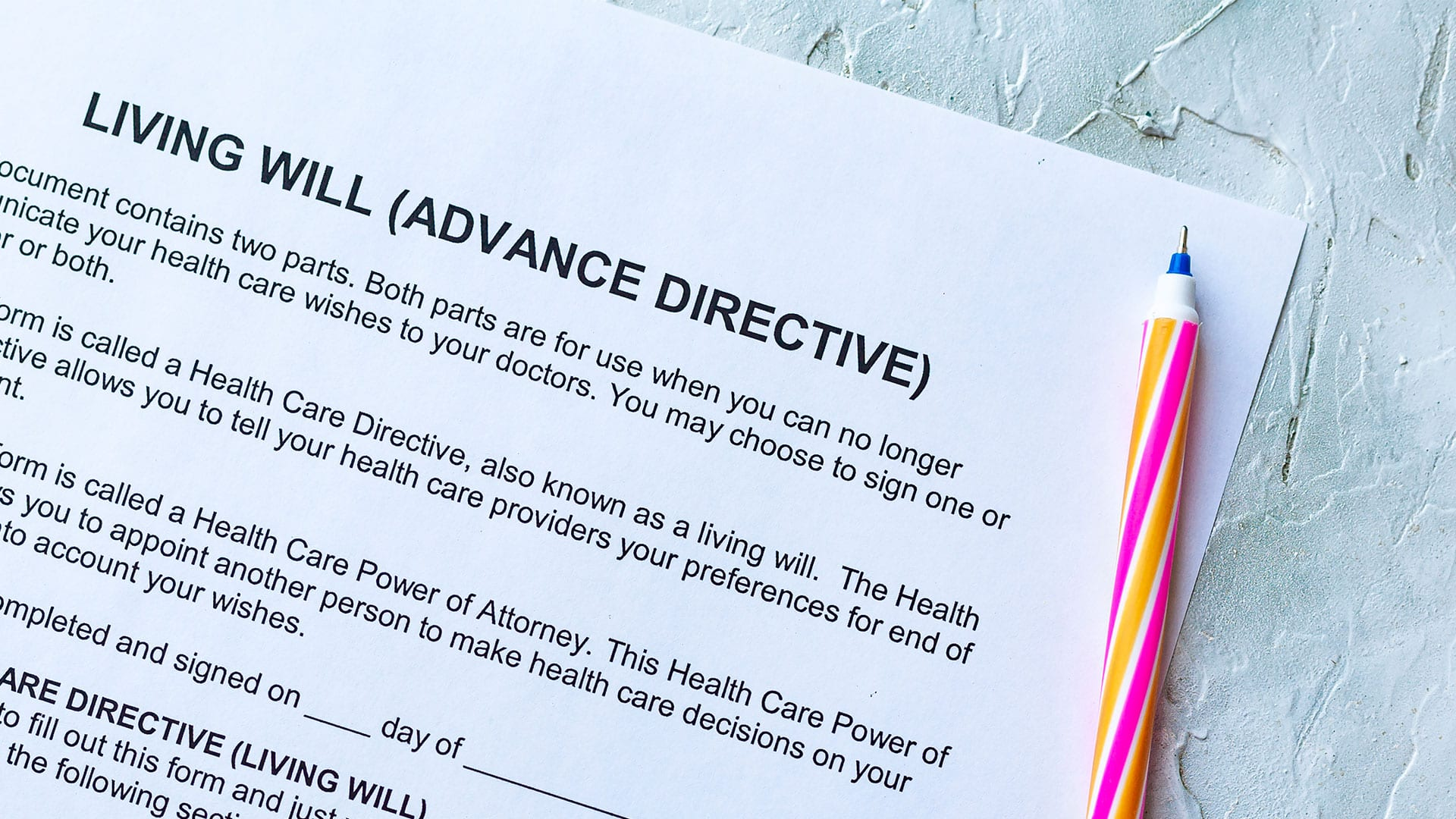 A blank advance directive sits on a table beside a pen.