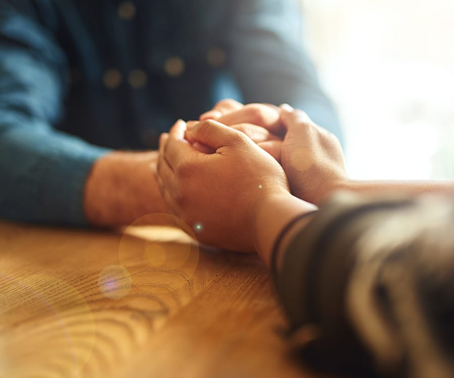 Spiritual support is provided as two people hold hands to give comfort.