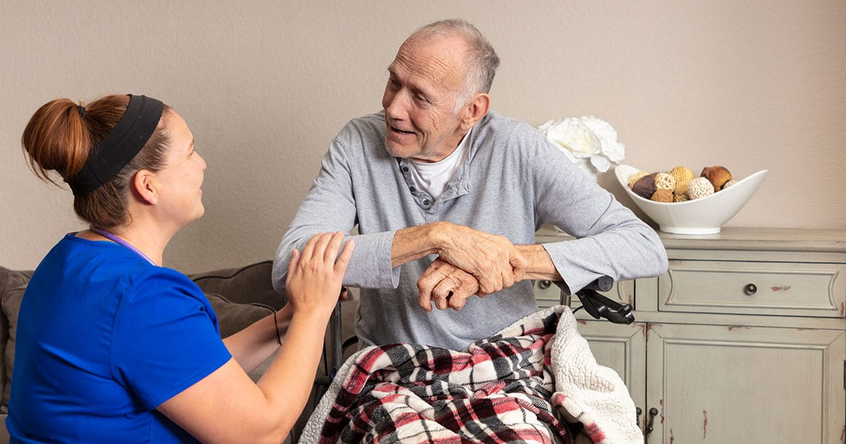 An older man in a wheelchair talks with a nurse in blue scrubs while in hospice