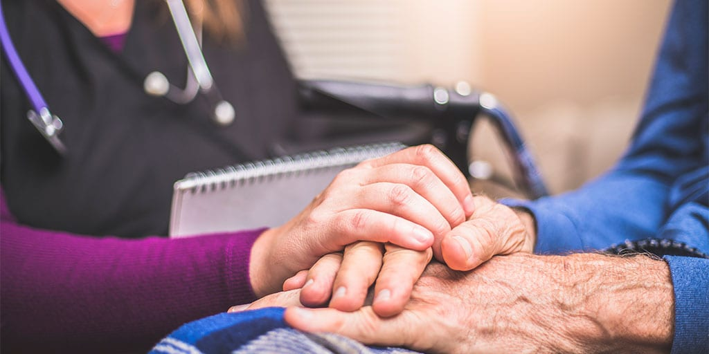 A hospice nurse with a notebook puts her hand on an elderly male patient's hand