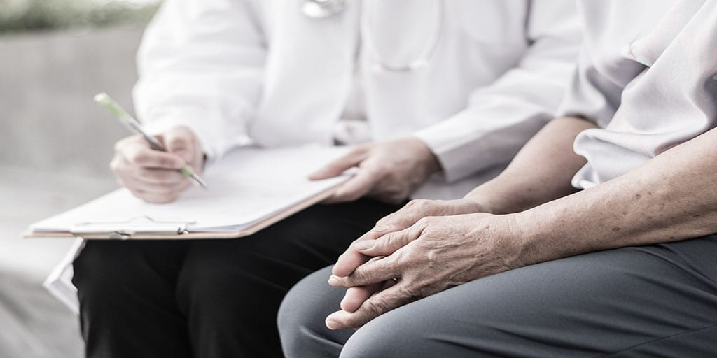 An older woman sits with a doctor as he takes notes on a clipboard for her dignity therapy