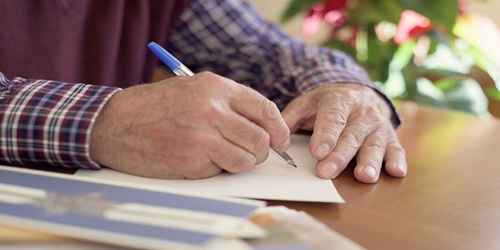 Elderly man contemplates what to write to someone in hospice