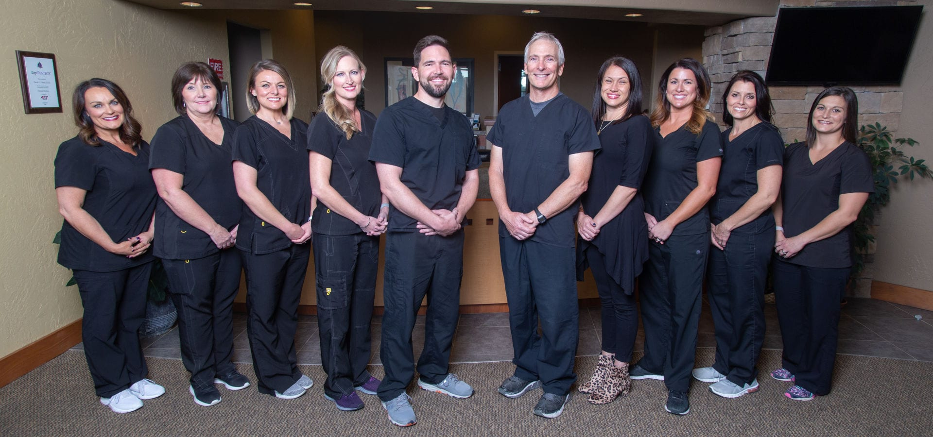 Dental office staff stand in front of the reception counter to pose for their photo, dentists at front center.