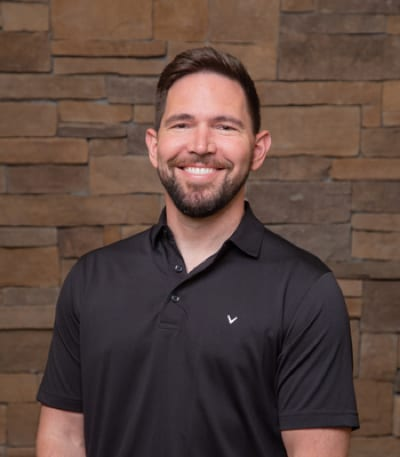 Dr. Kufahl poses for his headshot with a youthful energy and smiles from ear to ear with a pearly white grin.