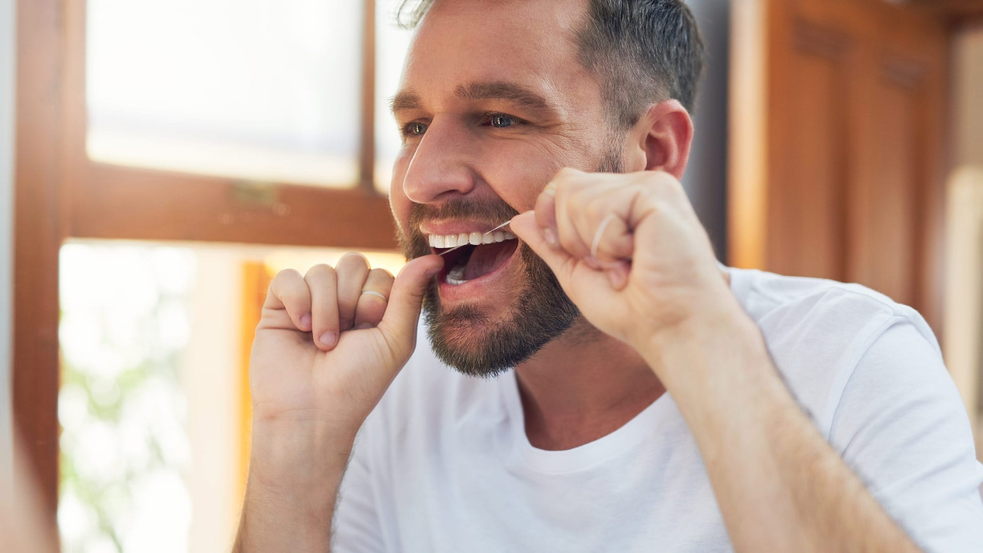 A man with healthy looking teeth and gums practices good dental hygiene by flossing in front of a mirror.
