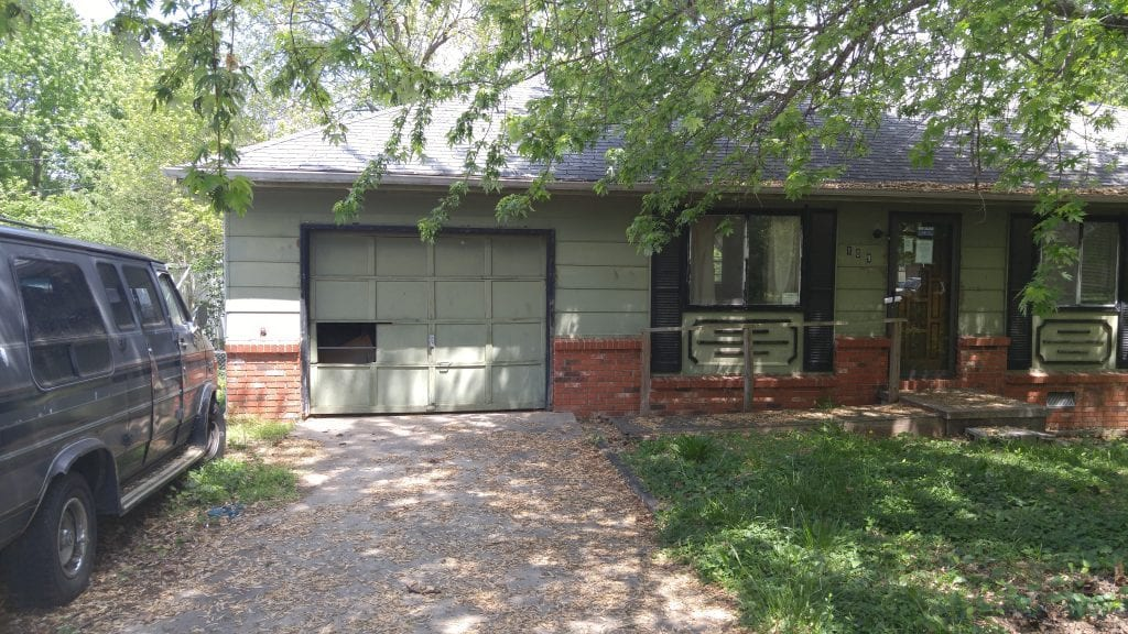 Before: an outdated exterior with a broken garage door