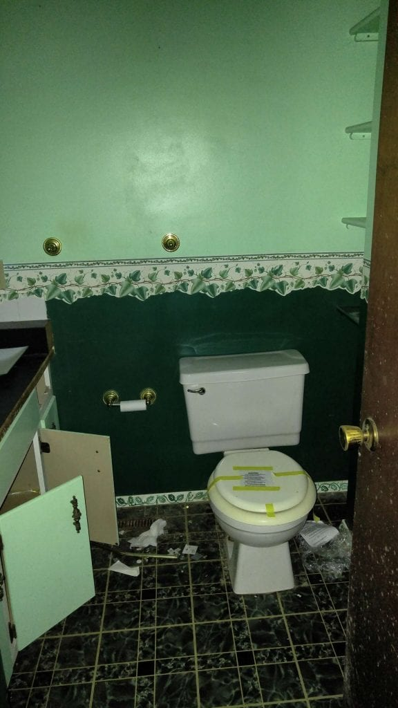 Before: a very outdated bathroom, with old tile and 1970s wallpaper