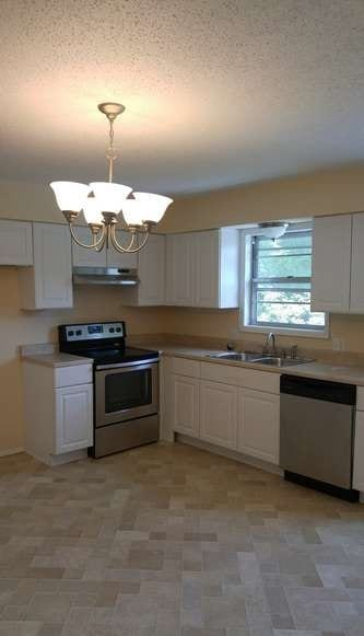 After: a modern kitchen with new tile, cabinets, and modern appliances