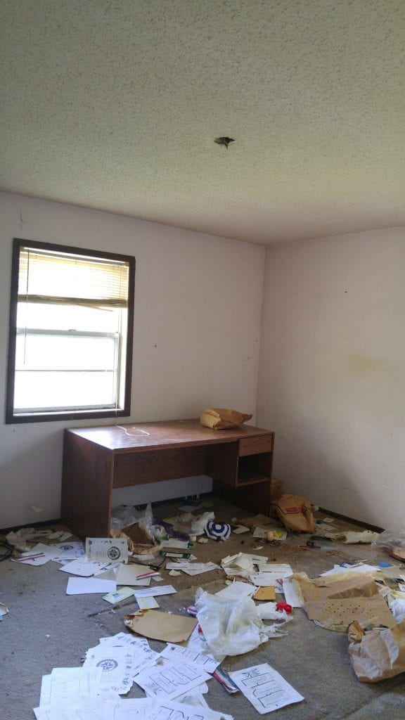 Before: a messy room with outdated paint and old carpet