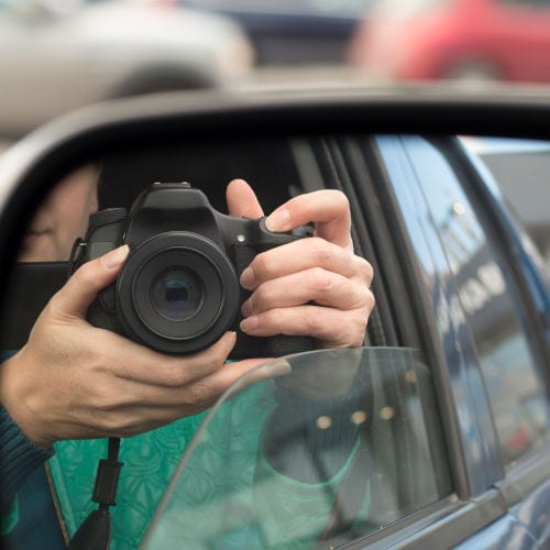 Hidden photographing. Reflection in car mirror of woman with camera.