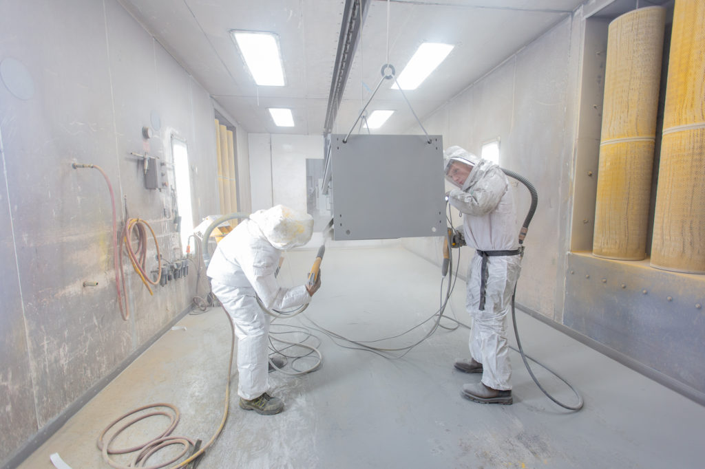 two men wearing protective gear completing powder coating on metal part