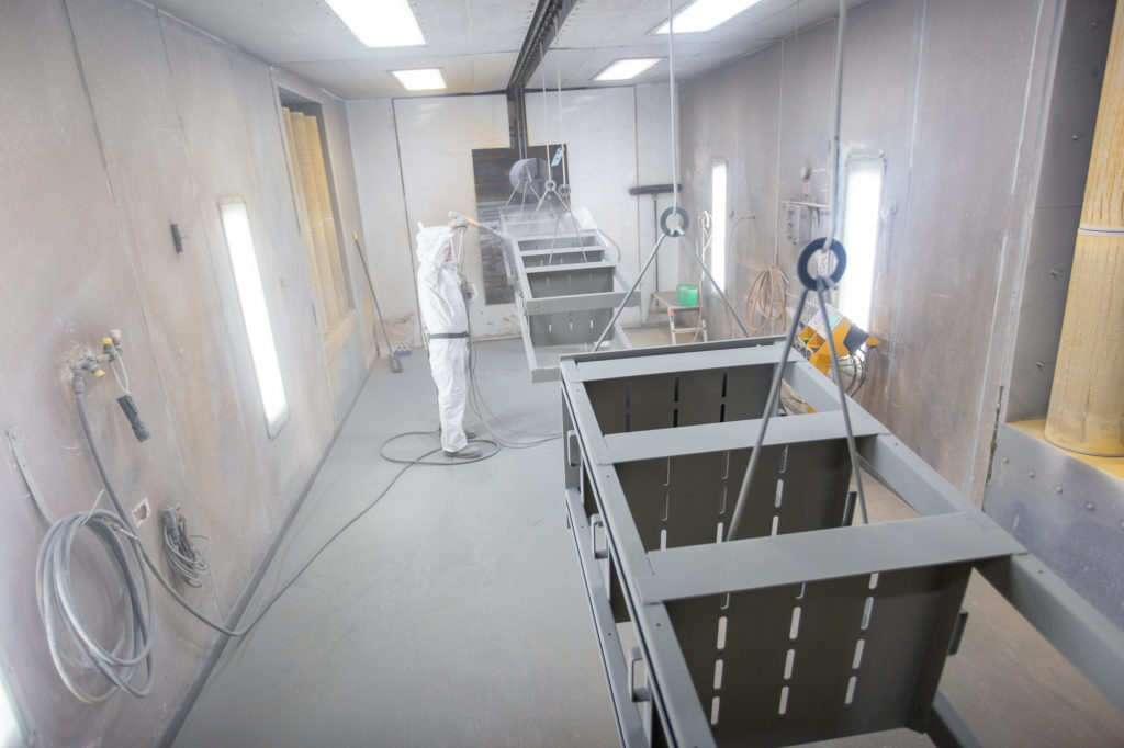 man wearing protective gear completing batch powder coating on multiple metal parts