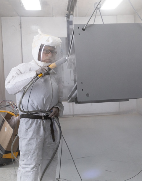man wearing protective gear completing powder coating on metal part